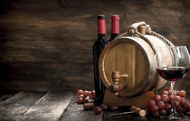 Table à vin. une barrique de vin rouge et de raisins frais. sur une table en bois.