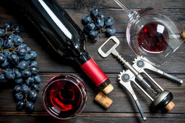 Table à vin. vin rouge avec tire-bouchon. sur une table en bois.