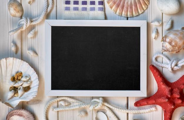 Tableau blanc avec coquillages, corde et étoile de mer