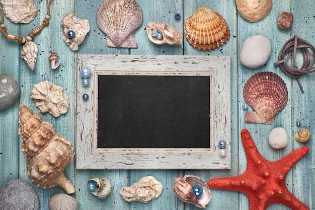 Tableau blanc avec coquillages, pierres, corde et étoile de mer sur bleu