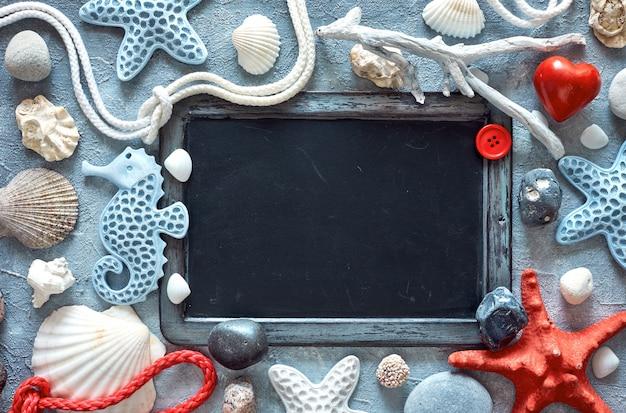 Tableau blanc avec coquillages, pierres, corde et étoile de mer sur texture bleu clair