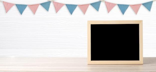 Tableau blanc debout sur les drapeaux de la fête colorée suspendus sur un fond de bois blanc avec espace de copie pour le texte