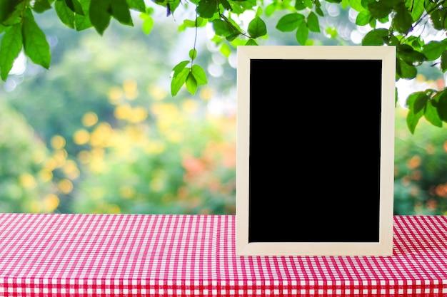 Tableau blanc debout sur la nappe à carreaux rouge sur fond de l'arbre de flou, espace pour le texte, maquette, montage de l'affichage du produit
