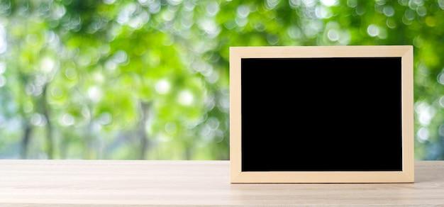 Tableau blanc debout sur une table en bois sur fond de l'arbre de flou, espace pour le texte, maquette, montage de l'affichage du produit