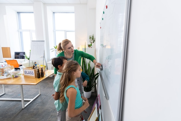 Tableau blanc avec des écoliers. enseignant aux cheveux blonds debout près du tableau blanc avec des écoliers