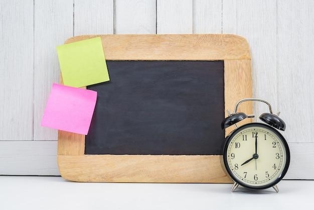 Tableau blanc de l'espace vide, réveil et pense-bête vide, note de poste sur bureau blanc
