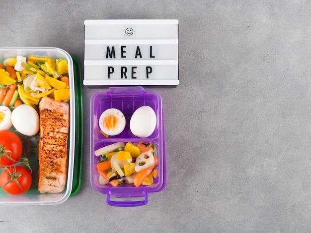 Tableau blanc avec inscription de préparation de repas près de nourriture dans des conteneurs
