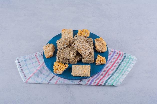 Tableau bleu de bonbons avec diverses noix et graines sur pierre.