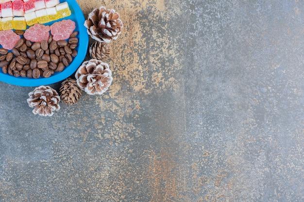 Un tableau bleu plein de différents bonbons à la gelée de fruits avec des pommes de pin. photo de haute qualité