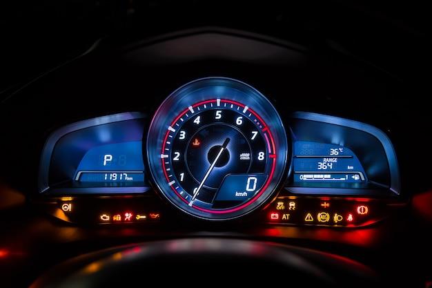 Tableau de bord des instruments de voiture moderne ou indicateur de vitesse et symbole complet dans la nuit