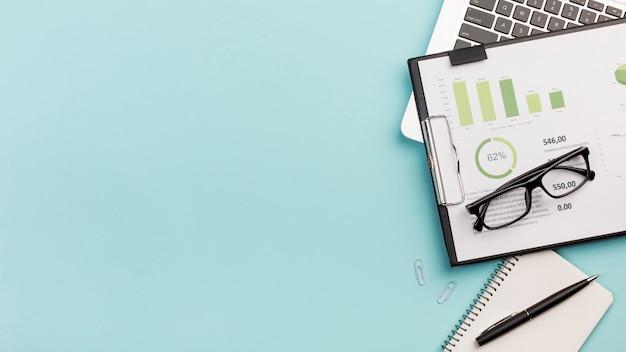 Tableau de budget d'entreprise et lunettes sur ordinateur portable avec bloc-notes en spirale et stylo sur fond bleu