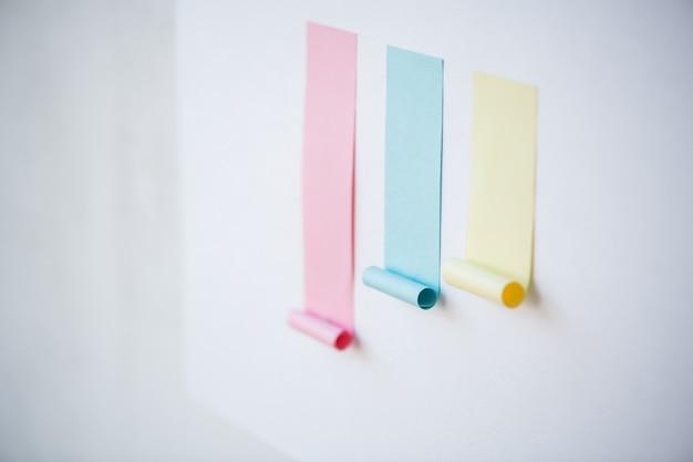 Tableau coloré composé de papier collant blanc rose et plus petit bleu et jaune collé sur un tableau blanc ou un mur