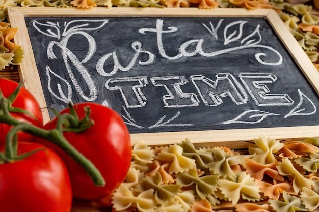 Tableau de craie signe pasta time sur une table en bois avec farfalle cru, tomates fraîches et poivre noir.