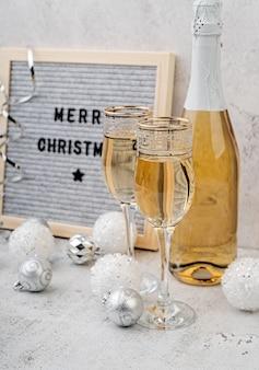 Tableau en feutre joyeux noël sur une table avec des verres de champagne et une bouteille