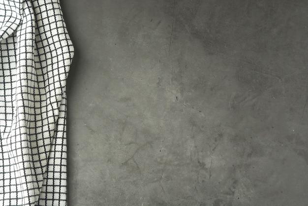 Tableau gris texturé avec tissu noir et blanc.