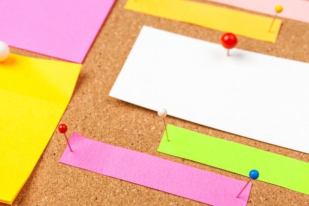 Tableau de liège avec plusieurs notes vierges colorées avec des épingles