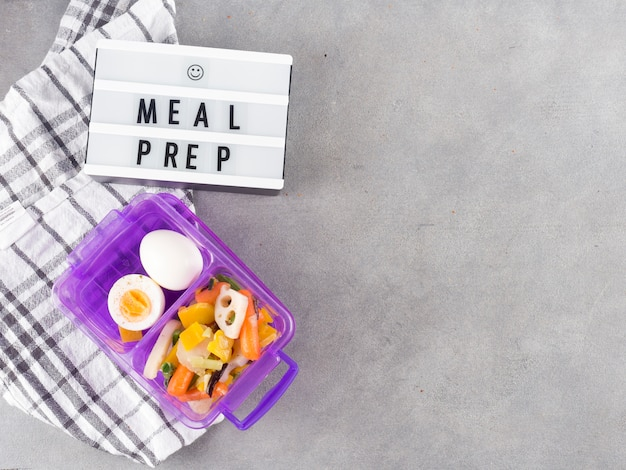 Tableau lumineux avec inscription de préparation de repas près de nourriture dans un récipient
