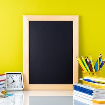 Tableau, manuels scolaires, horloge et fournitures scolaires sur la table près du mur jaune.