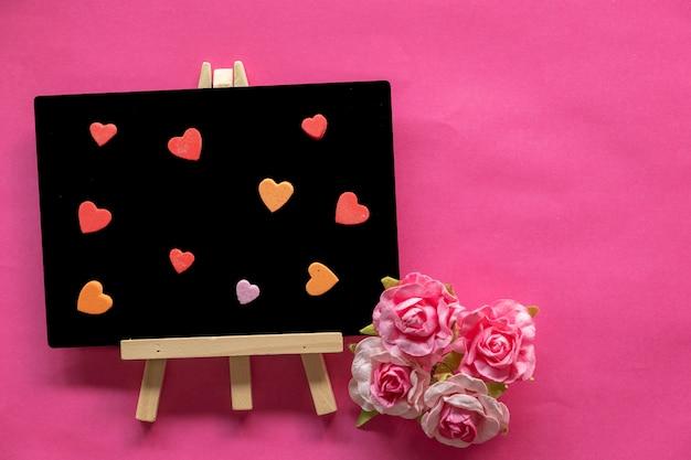 Tableau noir avec amour même coeurs sur fond rose