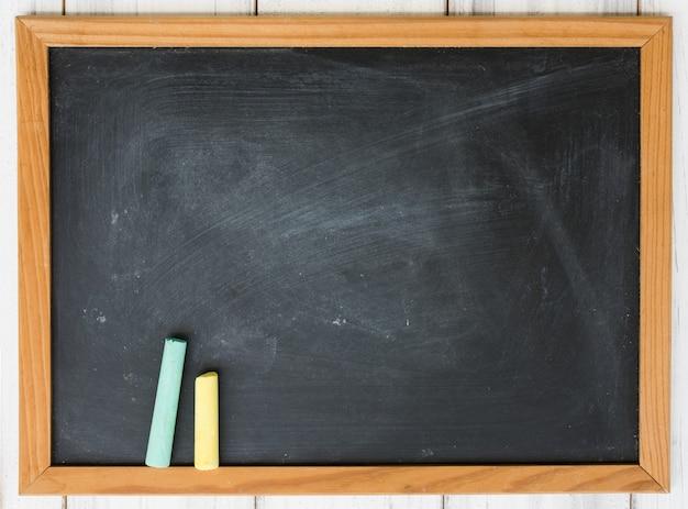 Tableau noir blanc et craie verte, jaune sur table en bois grunge