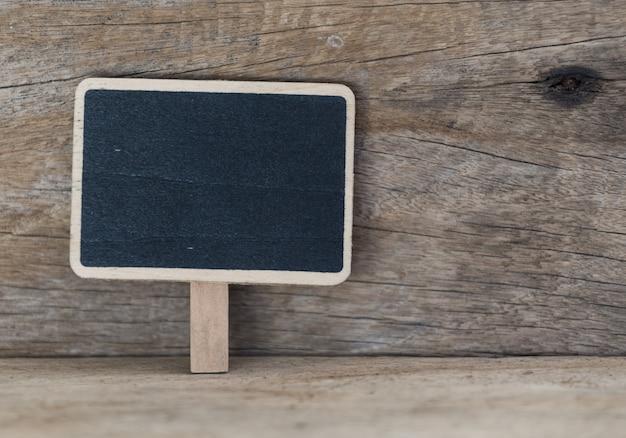 Tableau noir blanc sur fond de table en bois grunge
