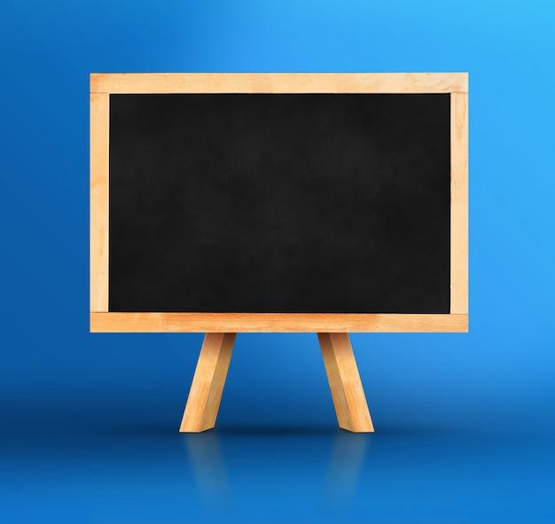 Tableau noir avec chevalet sur fond de studio bleu vif