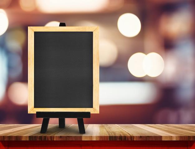 Tableau noir avec chevalet sur table en bois au café flou