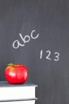 Tableau noir avec des chiffres et des lettres et une pomme et des livres