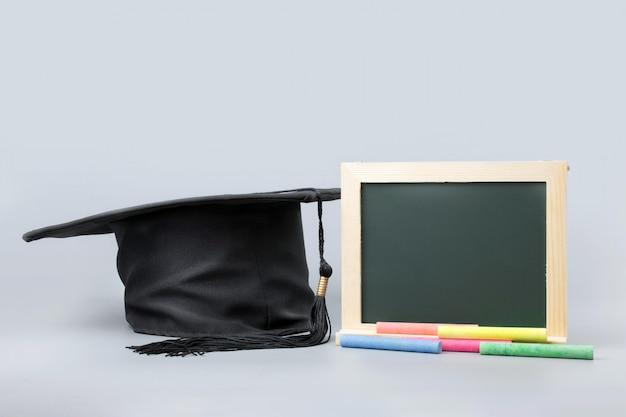 Tableau noir, craie avec chapeau de graduation sur fond propre.
