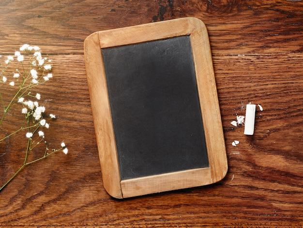 Tableau noir et craie sur table en bois.