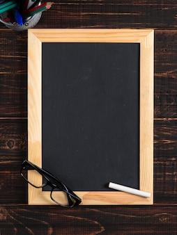 Tableau noir craie, verres et craie sur une table en bois, espace copie.