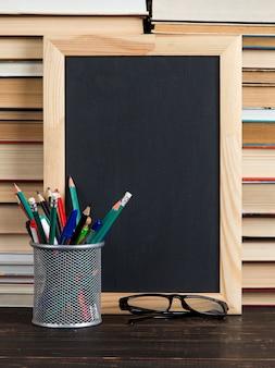 Tableau noir craie, verres, stand avec stylos, crayons et craie, contre livres, espace copie.