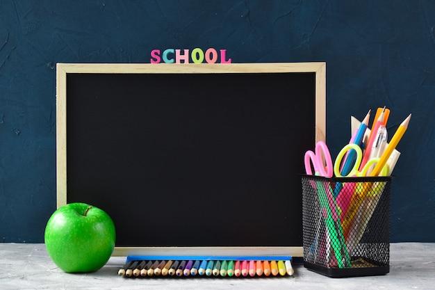 Tableau noir, crayons et apple
