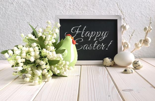 Tableau noir décoré de poules en céramique, d'oeufs et de fleurs de muguet, texte