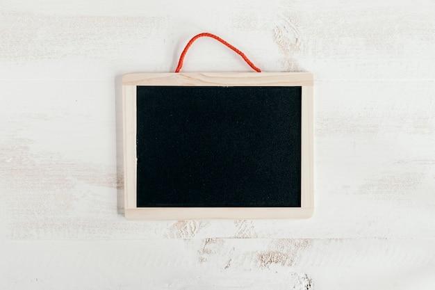 Tableau noir sur fond en bois blanc