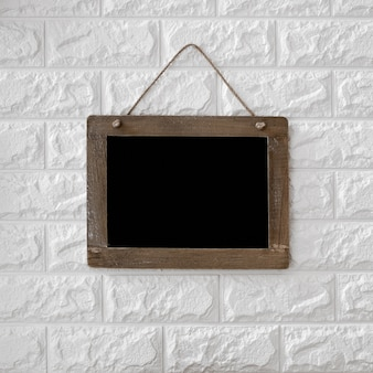 Tableau noir sur fond de mur de brique texturé