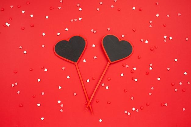 Tableau noir en forme de deux coeurs sur fond festif rouge