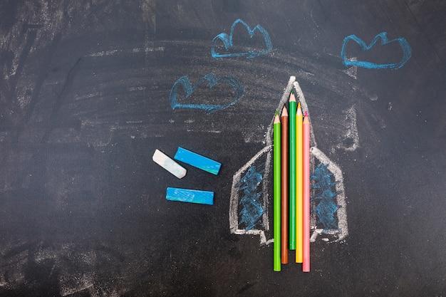 Tableau noir avec fusée et stylos