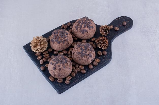 Tableau noir avec des grains de café, des biscuits et une pomme de pin sur fond blanc.