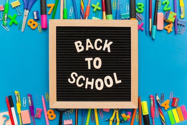 Tableau noir avec un groupe de fournitures scolaires sur un fond bleu.
