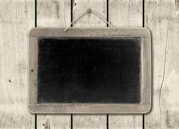 Tableau noir sur un mur en bois blanc
