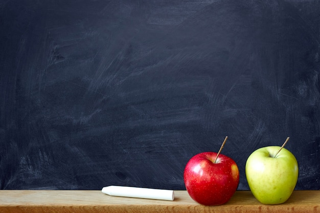 Tableau noir noir à la craie souille un tableau et deux pommes rouges et vertes, fond