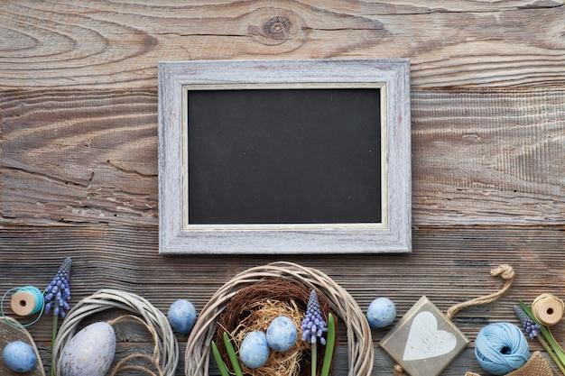 Tableau noir de pâques avec des oeufs de pâques, des fleurs et des décorations de printemps sur bois, espace de texte