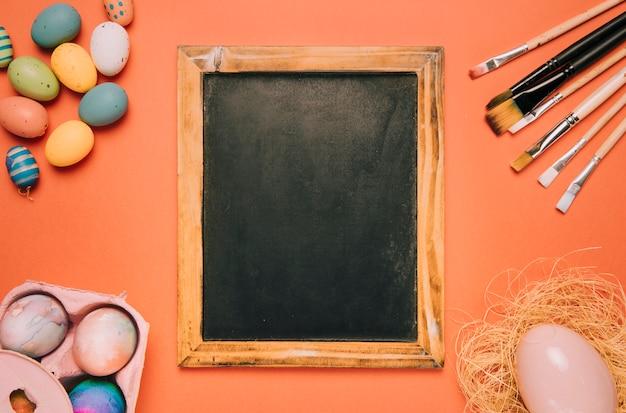 Tableau noir avec des pinceaux; oeufs de pâques sur fond orange