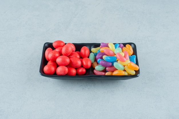 Un tableau noir plein de bonbons aux haricots colorés sur une surface blanche