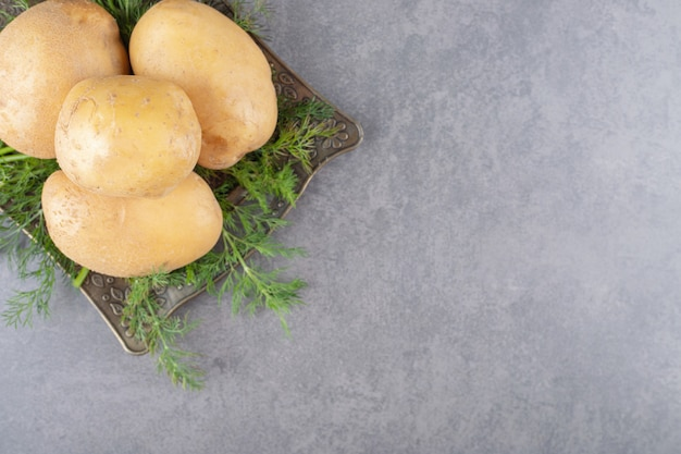 Un tableau noir de pommes de terre non cuites à l'aneth frais.