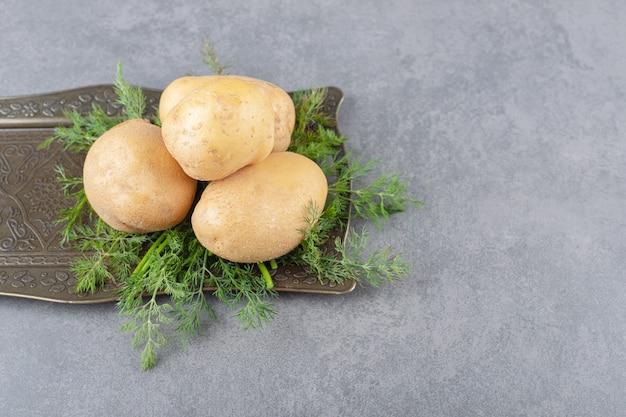 Un tableau noir de pommes de terre non cuites à l'aneth frais