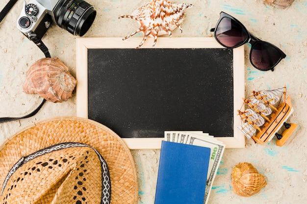 Tableau noir près du chapeau avec bateau jouet et argent parmi les coquillages et caméra
