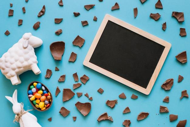 Tableau noir près des statuettes de pâques et des bonbons