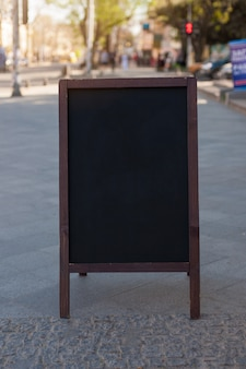 Tableau noir publicitaire dans la rue. place pour le texte, l'affiche ou l'information publique.